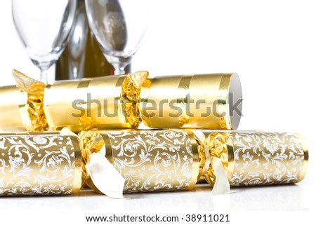 A closeup of gold christmas crackers, with a champagne bottle and 2 flutes in the background, isolated on white.