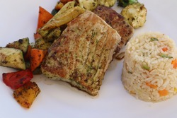 A closeup of grilled fish entree with rice pilaf and fresh vegetables on a plate