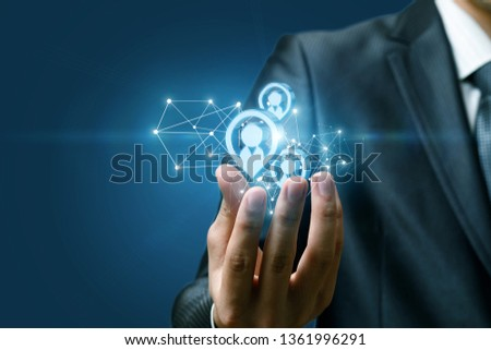 A closeup of hand of a businessman holding a structure of wireless connections and human figures images models at dark background. The concept of potential clients.