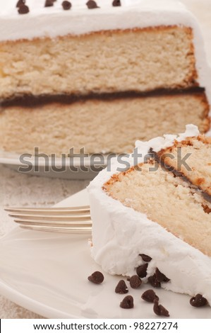 A Closeup of Home Made White, Double Layered Cake with Chocolate Filling, Seven Minute Allegretti Frosting with Chocolate Chips on Top.