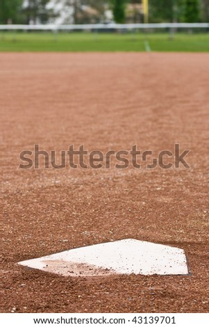 A closeup of home plate at a baseball diamond, looking out at the first base line towards the outfield.