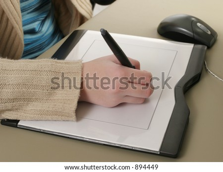 A closeup of one hand drawing on a computer graphics tablet.