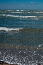 A closeup of sea frothy waves rushing towards the shore, scenic waterscape on the background