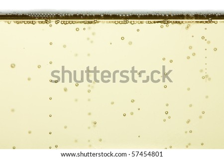A closeup of some champagne bubbles rising to the top of a glass.