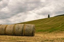 A closeup of some hay bales lying on a Tuscan hill.