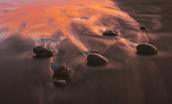 A closeup of stones on a beach with the sea on the background and the sunset reflecting on the water