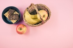 A closeup of tasty crackers with bread and fruits in a basket in the bowl on the pink surface