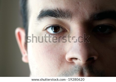 A closeup of the eye on a young man with a serious look on his face