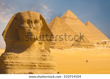 A closeup of the face of the Great Sphinx with a set of pyramids in the background on a beautiful clear blue sky day in Giza, Cairo, Egypt. Horizontal copy space