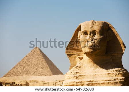 A closeup of the head and face of the Great Sphinx together with the Pyramid of Menkaure in the distance in Giza, Cairo, Egypt. Horizontal copy space