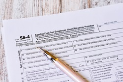 A closeup of the SS-4 tax form, Application for Employer Identification Number and a fountain pen on a wooden surface
