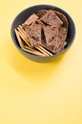 A closeup of the tasty salty crackers with slices of brown bread in the bowl on the yellow surface