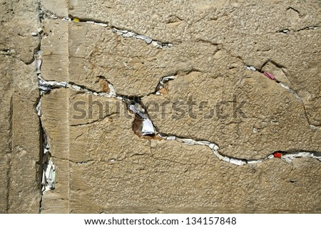 A closeup of the Wailing Wall in the old city of Jerusalem. In the cracks between the bricks there are numerous notes with pleads and requests from people to the Hebrew God.