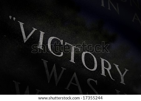 A closeup of the word VICTORY engraved on a war memorial.