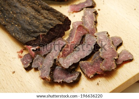 A closeup of traditional south african biltong on a wooden chopping board Stock photo ©