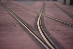 A closeup of tramway tracks under the sunlight at daytime with a blurred background