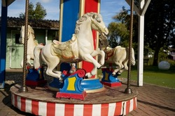 a closeup of white horse of merry-go-round carousel at the park on a sunny day