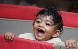 A closeup phot of an adorable indian toddler baby boy smiling with dimple in cheeks and standing inside a playpen.