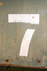 A closeup photo of the number 7 painted in stencil on a green steel dumpster.