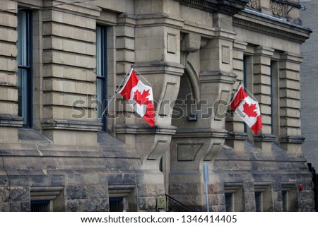 A 2019 closeup photo of two Canadian Flags on the Office of the Prime Minister and Privy Council building in downtown Ottawa, ON, CAN.