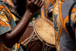 A closeup photo shows a drum and drummers hands being used in a kente yam festival in Ghana, West Africa.