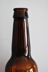 A closeup picture of a dark beer bottle neck