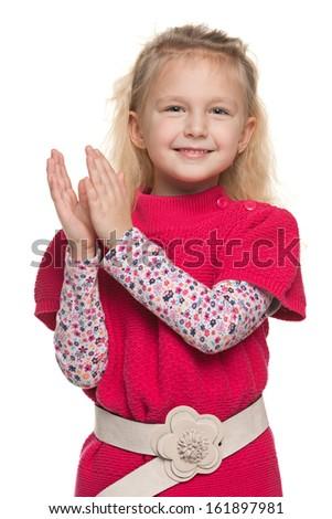 A closeup portrait of a cheerful little girl that applauds