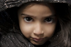 A closeup portrait of a cute young female with an innocent facial expression wearing a brown hood