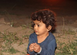 A closeup portrait photo of beautiful hindu little boy playing in garden at sunset , indian child , asian little male boy in nature