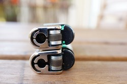 A closeup selective focus shot of two lighters on top of each other on a wooden surface