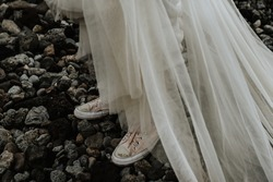 A closeup shot of a bride in a white dress wearing pink sneakers standing on rocks