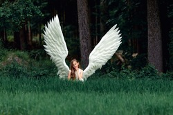 A closeup shot of a Caucasian blonde girl in angel wings costume in a meadow with trees