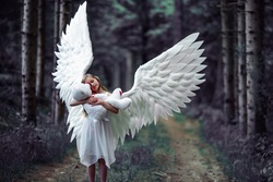 A closeup shot of a Caucasian blonde girl in angel wings costume with a teddy bear toy