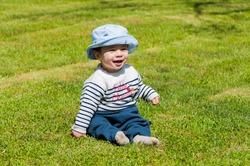 A closeup shot of a cute happy little boy in a hat sitting on a grass