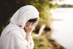 A closeup shot of a female wearing biblical robe crying  - concept confessing sins