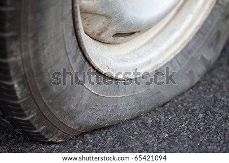 A closeup shot of a flat tire of a car