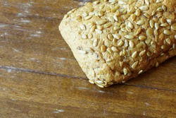 A closeup shot of a fresh bread with seeds on a wooden surface