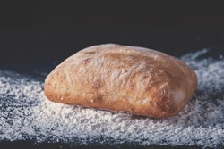 A closeup shot of a homemade freshly baked bread on a rustic table surface with spilled flour