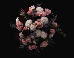 A closeup shot of a luxurious bouquet of pink roses and white, red dahlias on a black background