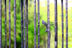 A closeup shot of a metal fence with a small bird figurine