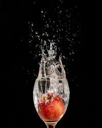 A closeup shot of a pomegranate sunk in the water glass