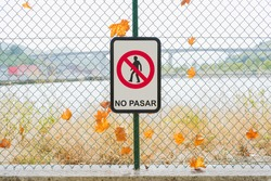 A closeup shot of a prohibition sign in front of a chain-link with autumn leaves, translation: