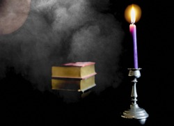 A closeup shot of a purple lit candle with books on the side with a black background