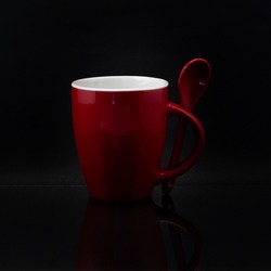 A closeup shot of a red mug with a spoon on a blackbackground