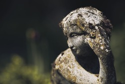 A closeup shot of a rust mossy stone statue of a female on blurred background