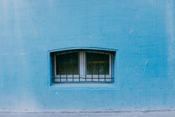 A closeup shot of a small window with metal bars in a blue painted wal