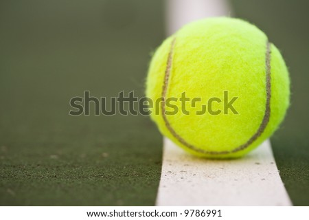 A closeup shot of a tennis ball in a tennis court