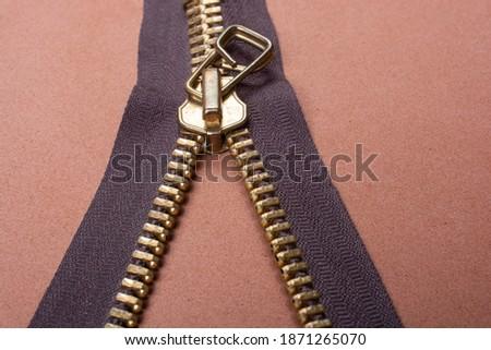 Photo of  A closeup shot of a zipper on a brown surface