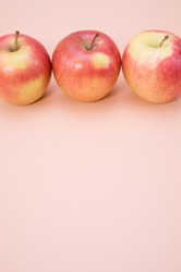 A closeup shot of aligned fresh apples isolated on a pink background