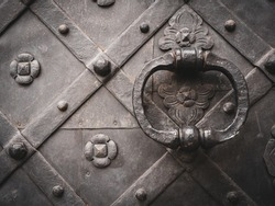 A closeup shot of an ancient door in black with metal handle